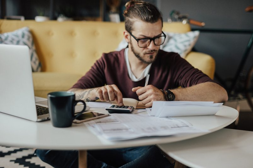 Here are 5 financial actions to take before you're 30, like this man calculating his finances at his living room table.