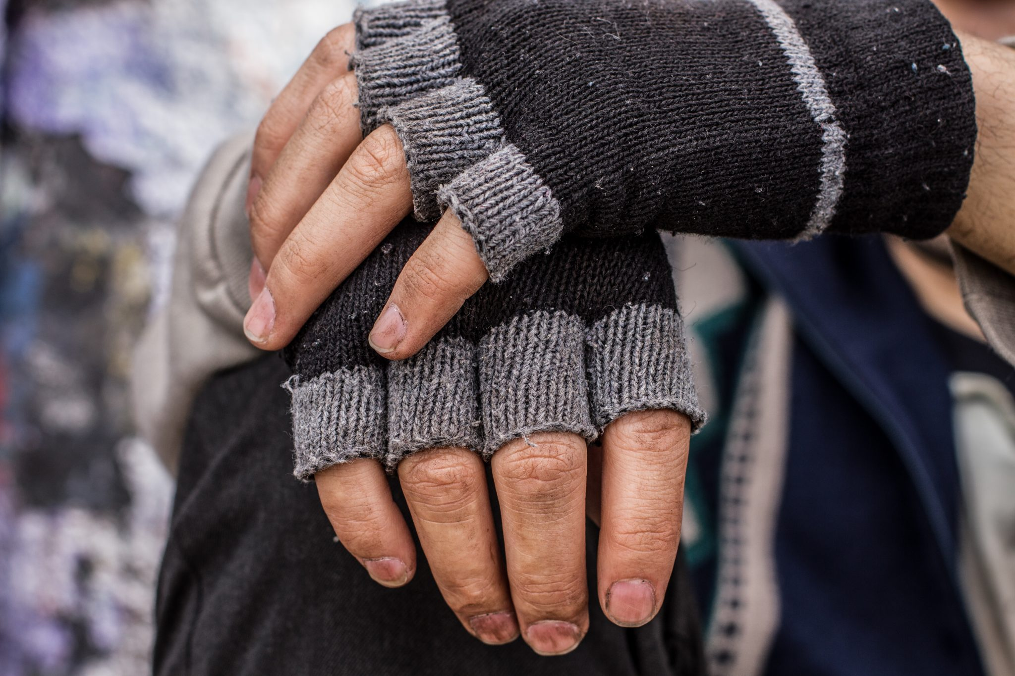 Close up photo of a man's dirt-covered hands wearing fingerless gloves.